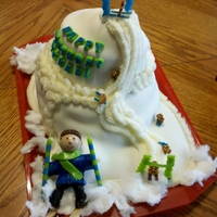 This multi-layer downhill ski slope has tiny gingerbread men (sugar) on skis.  The top and bottom gates are candles, as are the big skier's ski poles.  Obviously a plastic head, but this is my first attempt at a gumpaste body!  Thanks for looking!  Please share with me how you found or searched to see this picture!  I'm curious ! :)