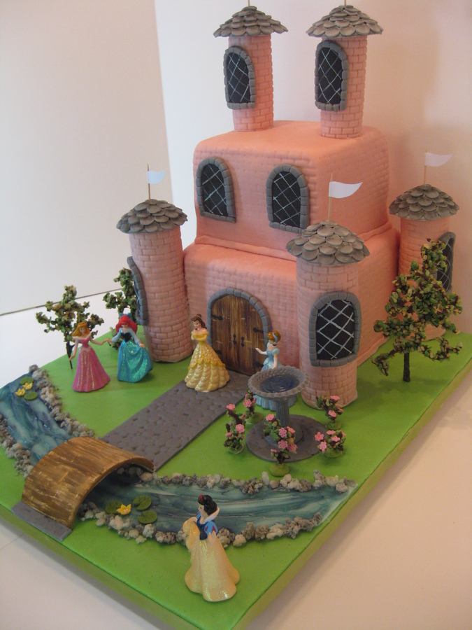 Emma couldn't decide which Disney princess was her favorite, so all were invited to the party at the pink castle. Since this is a friendly castle, there is no drawbridge over the piping gel moat--- rather, a welcome bridge.   The cake is WASC with strawberry buttercream, and strawberry MFF over white ganache. The towers are RKT topped with gumpaste slates. The trees and rosebushes are chocolate covered grape stems dipped into green rice krispies for leaves. Water lilies and roses are gumpaste, as is the birdbath filled with piping gel.   I had so much fun making this cake that I had to hold myself in check, not to over-do.  The client provided the figurines.