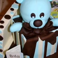 This cake was for a friend having her first baby at 40 after a long road of disappointment.  I wanted to make something special for her.  The box cake is two chocolate mud cakes split and tiered then covered in sheets of fondant.  The stripes were added over the blue base.  The teddy bear is a lemon sour cream cake with fondant accents and bow.