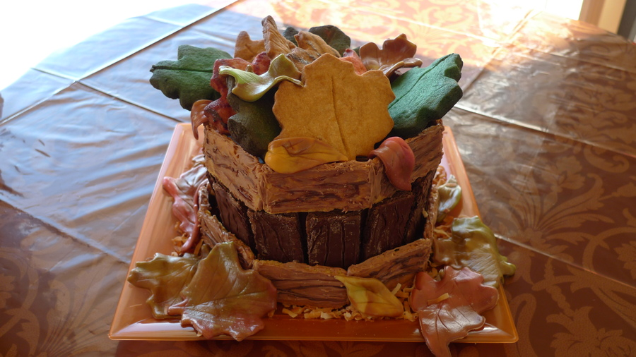 Leaves are cookies and tootsie rolls, bushel is made from the bottom half of the giant cupcake pan and the wood slats are different flavor chocolate covered graham crackers.  Toasted coconut for dried grass.  No fondant!