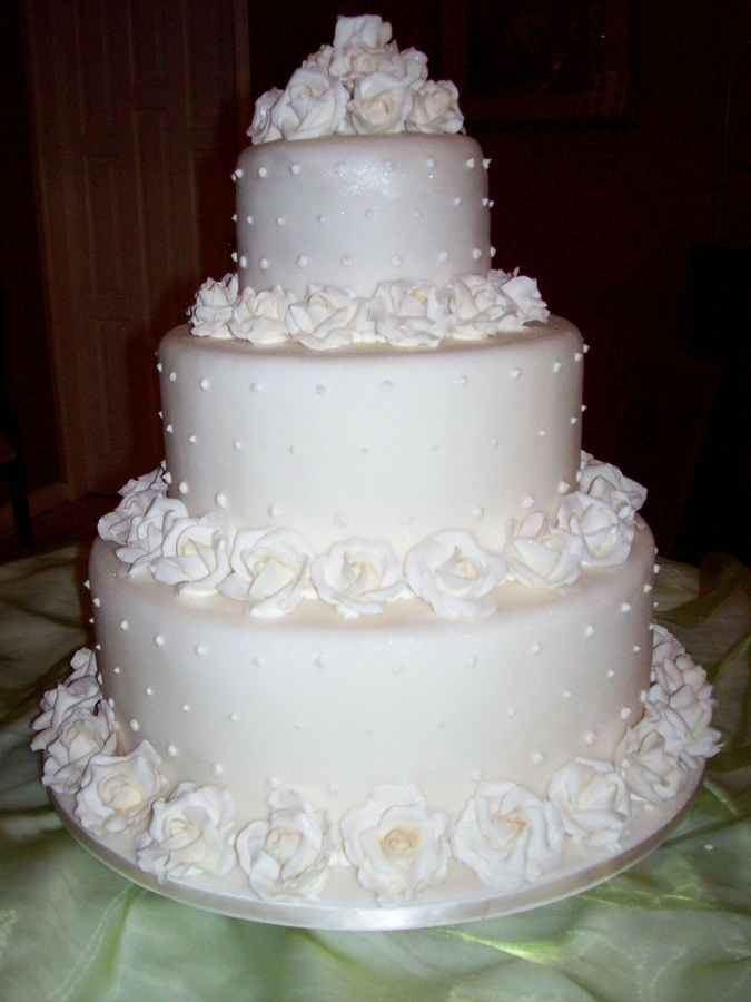 "White on White Wedding cake.....Bride wanted a 'Katie Holmes and Tom Cruise replica - only smaller.....design similar to Wilton Wedding Cake Book cover - minus the ceramic topper.....This was done using a 14"", 10"" and 6 "" fruit cake, gumpaste rose,s, dusted in 'superpearl' dust.  A total of 82 roses in 3 different sizes used to complete this cake.  Bride is thrilled!!!!"