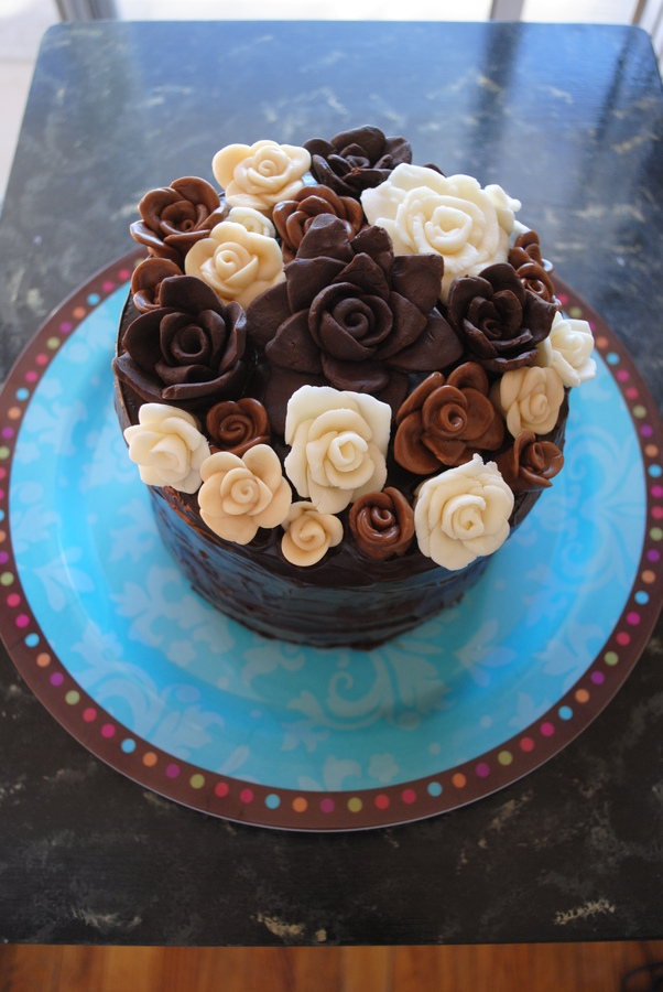 7 layer cake covered in ganache and decorated with modeling chocolate and tootsie roll roses!