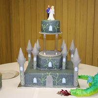 Castle Wedding wedding cake for my niece, dragon form is foil wrapped in fondant and airbrushed.
