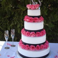 Rose Wedding   Hidden pillar wedding cake with Med. Pink Roses. Smooth frosted buttercream cake