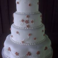 Beth Wedding Cake   White cake with buttercream, fondant covered and flowers.