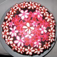 Flower Cake Top View chocolate cake with oreo filling, frosted with raspberry imbc, covered with chocolate mmf, and decorated with pink, red, and white...