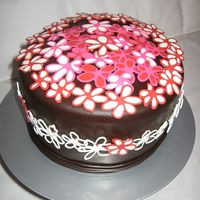 Flower Cake chocolate cake with oreo filling, frosted with raspberry imbc, covered with chocolate mmf, and decorated with pink, red, and white...