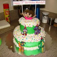 "Dora Birthday Cake   Yellow cake, frosted with bc. 10"" bottom tier, 6"" top tier. Characters are chocolate transfers."