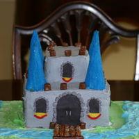 Castle Cake  Castle Cake for my 6 year old son's bday. 3 8x8 layers stacked for bottom portion, then 2 2x2 pieces stacked for top. Ice cream cones...