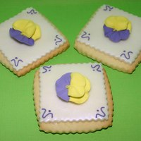 Pansy Cookies Sugar cookie with rbc. Dusted with violet pearl dust. Decorated with royal icing flower.