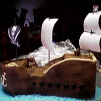 "Pirate Ship 16"" L x 6"" W x ? H WASC cake covered with fondant. Non-edible sails, BC ""water"". Treasure chest, rope, anchor, barrel,..."