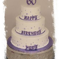 60Th Birthday   White Cake With Raspberry Filling and White Almond Whipped Icing. Decorations are White Chocolate.
