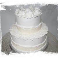 Small Wedding  This was buttercreme icing witht he top layer Ghirardelli Chocolate Cake and the bottom Amaratto White. The border is MMF with pearl dust...
