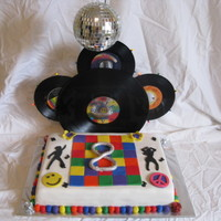 70's Disco Birthday Cake I used real records for the background and put twinkling lights around the little records. The disco ball hangs over and has a light that...