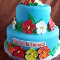 Hawaiian Bday Cake My first real cake covered in fondant. I don't know if I will do another one, but who knows. MMF with gumpaste flowers and EI words on...