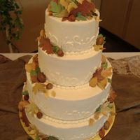 Fall Wedding Cake 4 tier wedding cake with buttercream icing and gumpaste leaves in multiple colors.