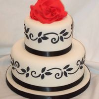 Jamie's Cake Fondant cake with royal scroll and flower design. Fondant giant ribbon rose on top.