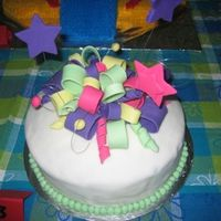 Cake Contest - 2Nd Place Most Decorative  Covered in white fondant. Made bow loops in all different sizes and widths with bright fondant pack and pastel green. Made stars in 2...