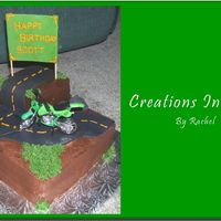 Motorcycle Cake  This is a chocolate cake with raspberry filling and chocolate buttercream. The road, rocks, and sign are fondant and I cheated and got the...