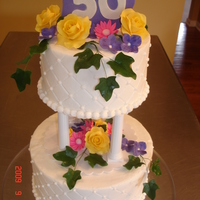 50Th Anniversary Wanted to replicate an older cake w/the pillars. Buttercream iced, gumpaste flowers, ivy and plaque.