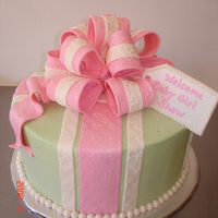 Pink And Green Buttercream iced w/fondant stripes, bow and pearls.