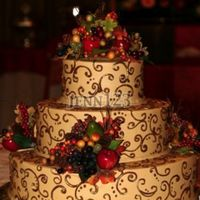 Fall Wedding Chocolate cake with peanutbutter filling. Tan icing with brown and painted gold accents. Silk/plastic fruits and greenery.