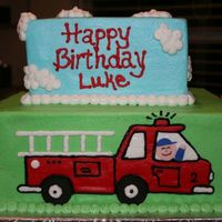 Fire Truck Cake 10 in and 8 in square iced in buttercream, fire truck on front, fire hydrants and tree on back, and firefighters on the sides putting out...