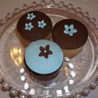 Blue And Brown Cupcakes These were for a bridal shower. Cupcakes were covered in buttercream and topped w/ fondant circles and flowers. Thanks for looking!