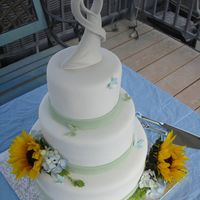 Sunflower Wedding Cake   Vanilla rum cake covered in fondant. Gumpaste butterflies and real flowers. Thanks for looking.