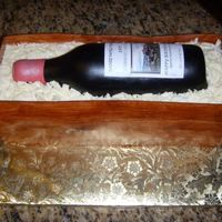 "Wine Bottle Cake WASC chocolate cake with chocolate mocha icing. Gumpaste bottle with fondant woodgrain crate. Many thnaks to everyone on CC""s help!"