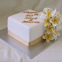 Anniversary Cake 6 inch caramel mud cake covered in white fondx and gumpaste lettering and flowers with fabric ribbon. Frangipani and stephanotis (sp)...