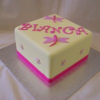 Square Lemon And Pink 6 inch mud cake covered in lemon yellow fondx with fabric ribbon.