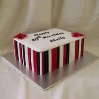 Black, Red And White 7 x 9 inch white chocolate mud cake covered in white fondx and then covered in fondnt stripes. Gumpast lettering. Made at customer rqst.All...