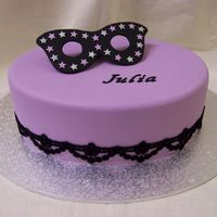Masquarade Cake 11 inch oval caramel mud cake covered in violet fondx and gumpaste lettering. Mask is also gumpaste. Lace is fabric as supplied by lady...