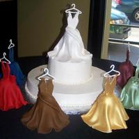 Bride And Maids  Two tiered cake. topped with a smaller cake covered with a fondant dress. Cake is surrounded by small dome shaped cakes covered with...