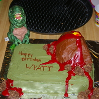 Wyatt's Dino Cake Dinosaur cake iced in buttercream. Volcano made out of RKT & iced in buttercream. Lava made with Wiltons sparkly gel.