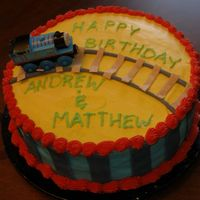 Thomas Train Birthday Cake Birthday cake for my 2 and 4 year old. They loved it. Iced in buttercream with fondant tracks and stripes. Thomas wooden toy.