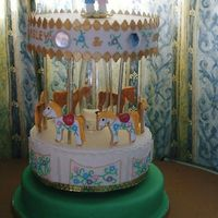 Carousel Wedding Cake designed for my sister who met her partner while working at a theme park. The horses are NFSC cookies and to top it there is a very thin...