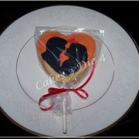 Sunset_Silhouette_Cookie-Cc.jpg Heart shaped sugar cookie pop decorated with Alice Cookie Icing. Depicting a silhouette of a couple embracing at sunset. Overpiped to give...