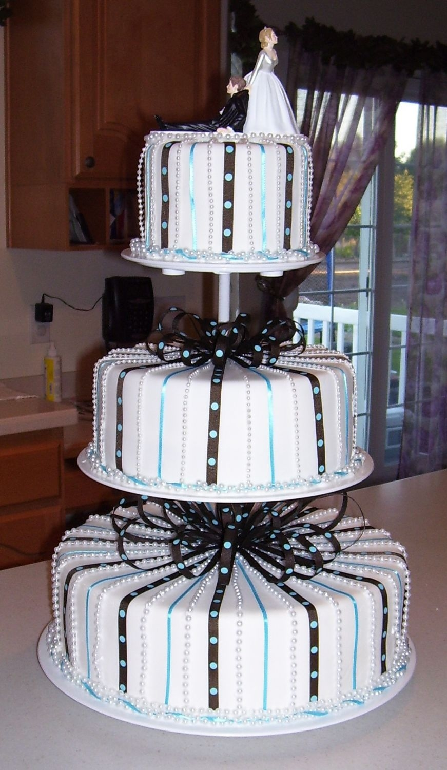 Blue And Brown Wedding Chocolate cake covered with fondant with blue and brown ribbons. Pearls between ribbons.