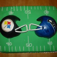 Super Bowl 40 This cake is covered in marshmallow fondant. The helmets were made with the sports ball pan and covered with fondant as well.