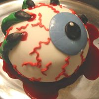 A Witch Holding An Eyeball this is made with the sports ball pan and marshmallow fondant