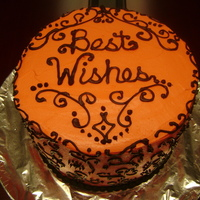 Best Wishes This is a 4 layer vanilla cake with tangerine-colored buttercream and chocolate swirl designs.