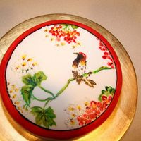 Bird Cake View of the chinese bird cake that is hand painted with food coloring. The picture is of a sparrow on a branch surrounded by red and white...