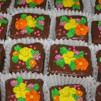 Chocolate Mini Cakes milk chocolate cake with chocolate buttercream filling and iced with chocolate. royal icing flowers