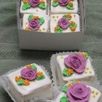 Mini Flower Cakes white modified cake with wedding bouquet flavor added. torted half a sheet cake and filled with rasberry filling then cut into 2X2 squares...