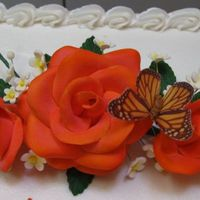 Coral Roses gumpaste roses, leaves, and white filler flowers. airbrushed the roses with an orange and pink color that i made. then i dusted the inside...