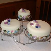 Nana's 80Th All cakes were of different flavors but covered in vanilla bc and covered with MMF. Royal icing flowers (colors pulled from the ribbon...