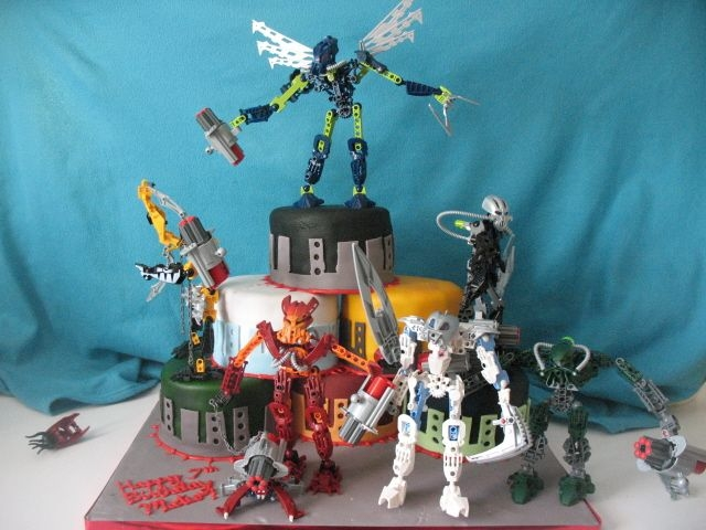"Bionicle Cake, Designed By A 7 Year Old. My son's b-day cake. His design, down to the red RI ""spikes"". 6"" rounds stacked in a pyramid. He placed the Bionicles..."