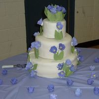 "Tulip Wedding Cake   This is a 14"", 10"", 6"" stacked cake, covered in MMF with gumpaste tulips and leaves."
